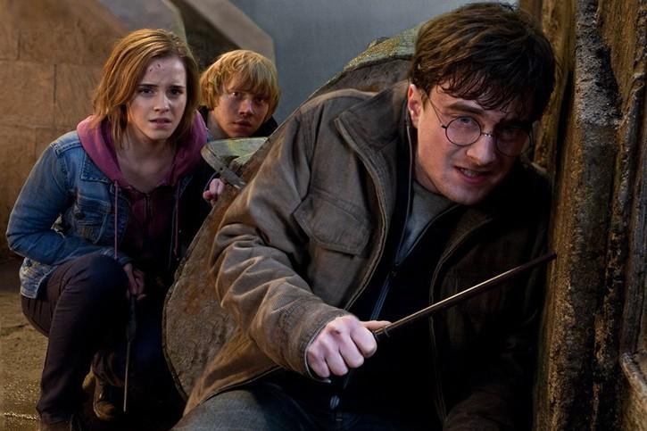 Harry Potter, Ron Wesleay et Ermione se protégeant derrière un mur