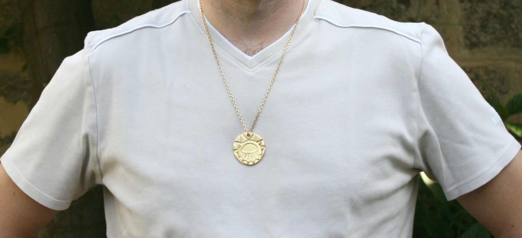 Le médaillon des Mystérieuses Citées d'Or porté par un adulte