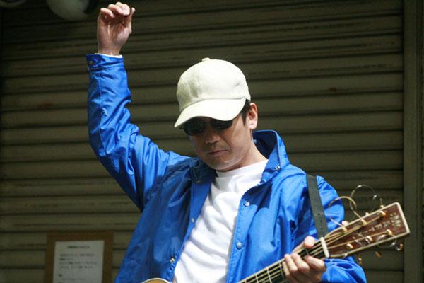 Kenji jouant de la guitare pour gagner sa vie