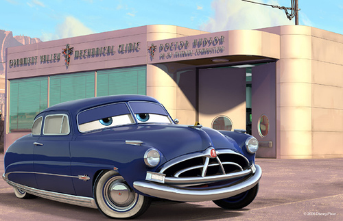 Doc Hudson (Pixar – Cars) Hudson Hornet devant son garage